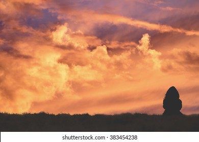 Silhouette of a girl watching the clouds after sunset.