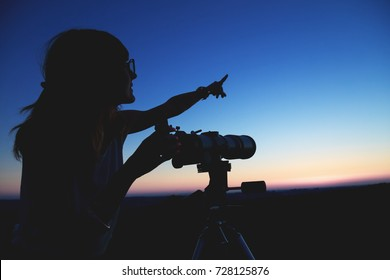 Silhouette of a girl while watching through the telescope.