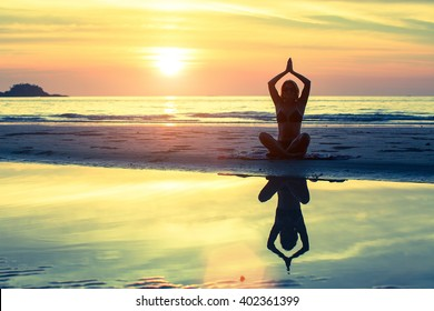 Silhouette of girl in yoga pose sitting on the beach during sunset.