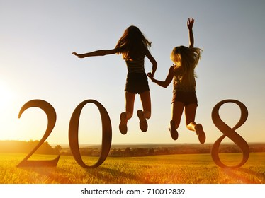 Silhouette of girls jumping up in the sunset at the celebration of New Year 2018.