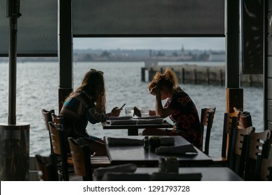 Silhouette of girls seating in a cafe near a pier