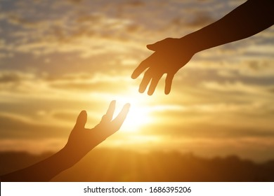 Silhouette of giving a helping hand, hope and support each other over sunset background.