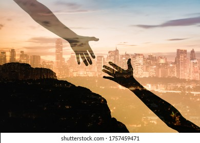 Silhouette of giving a helping hand, hope and support each other over sunset city background. Double exposure