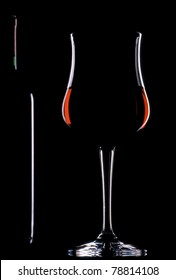 Silhouette of a glass of red wine and a half bottle