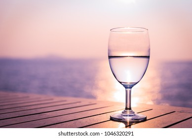 Silhouette glass of wine on a wooden table with  seascape and skyline in the evening with sunset tone style.