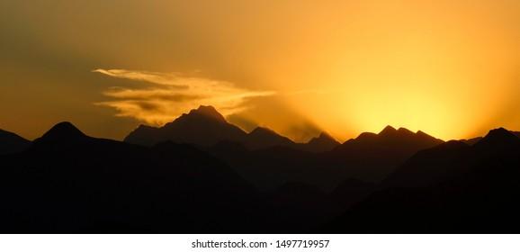 SILHOUETTE: Golden morning sun gently illuminates the mountain range in Himalaya. Scenic silhouettes of mountains of Tibet on a beautiful autumn evening. Evening sun hides behind a ridge in Himalaya.