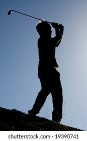 Silhouette of a golf player on the fairway