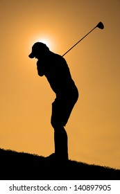 Silhouette of a golfer with a driver about to take a shot with an orange sky.