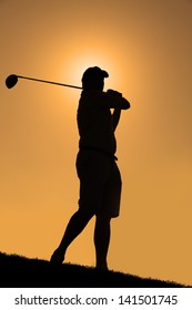 Silhouette of a golfer with a driver having taken a shot with an orange sky.
