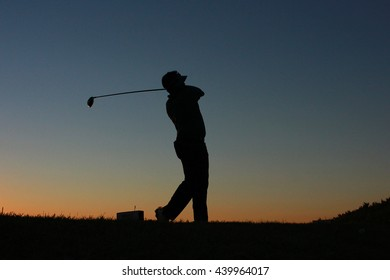 Silhouette of a golfer swing on the sunlight