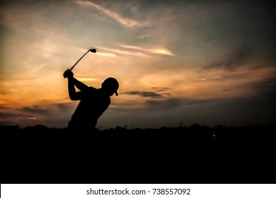 silhouette of golfers full swig during beautiful sunset.