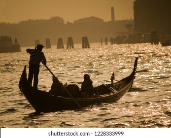 Silhouette of a gondolier paddling his gondola during sunset in Venice, Italy