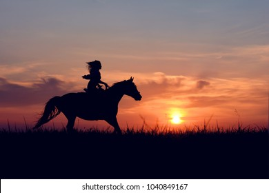 Silhouette of graceful girl, riding on galloping horse with red rising sun on horizon. Horseback woman on colorful sunset background.