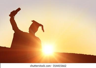 Silhouette of graduate against sun shining