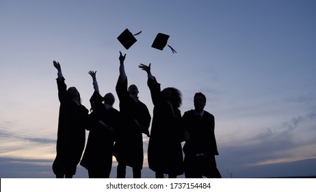 Silhouette of Graduating Students Throwing Caps In The Air.
