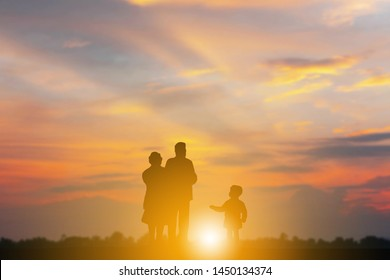 Silhouette of Grandfather grandmother and grandchild playing and walking evening sunset background, Happy family concept