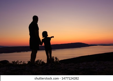 Silhouette of a grandfather and his granddaughter enjoying the sunset view at the sea on a Croatian coast