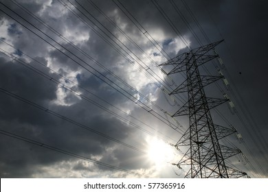 Silhouette of grid energy transmission tower against cloudy sky and sun burst