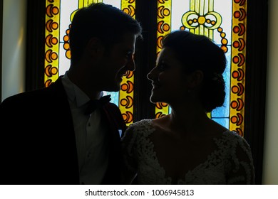 silhouette of groom and bride in front of window vitrali