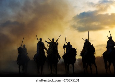 Silhouette of a group of Berber horsemen and the rifle in their hands.