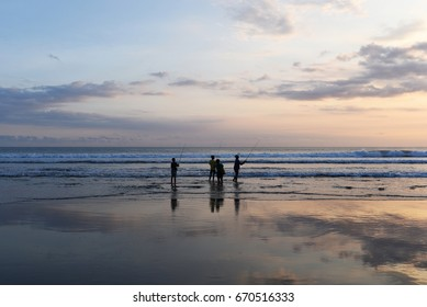 Silhouette group children fishing in ocean surf at sunset.