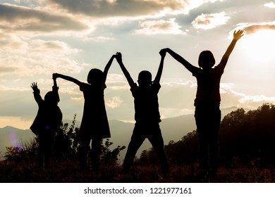 Silhouette group children with raised hands on mountain at sunset time.