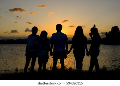 silhouette group of friends standing hand in hand in sunset.