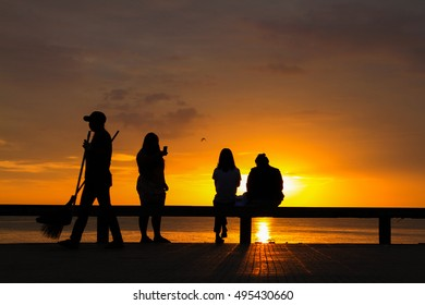Silhouette of group girls in the morning at the beach waiting for the sunrise.