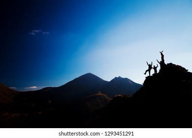 silhouette group of happy hikers on a rock