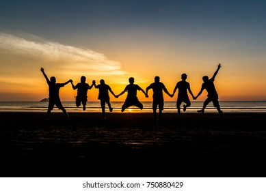Silhouette group of man traveler jumping and enjoying on sea beach at golden sunset time and action arms open felling freedom, Ranong beach, Travel in Thailand, Summer holidays vacation business trip