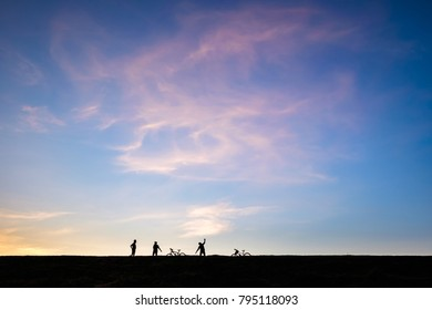 Silhouette group of men and bicycle come to the hill for exercise under the beautiful sky at sunset
