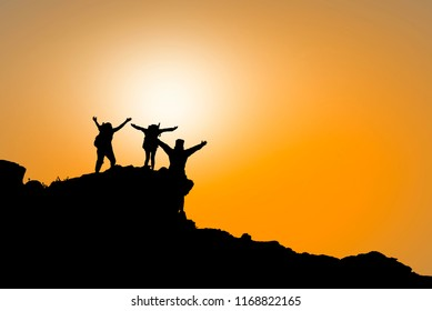 Silhouette of a group of people holding hands  up on the mountains with sunlight with a beautiful sunset - concept about family, friendship, teamwork, success and excitement