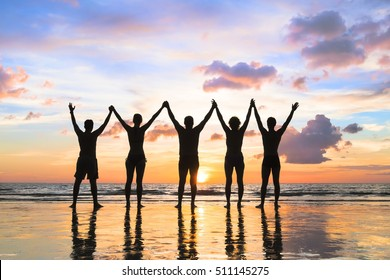 Silhouette of a group of people holding hands up on the beach with a beautiful sunset - concept about family, friendship, teamwork, success and excitement
