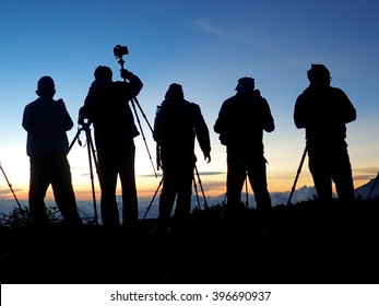 Silhouette of a group of photographers taking photos