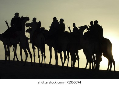 A silhouette of a group of Tuareg on their camels in the desert