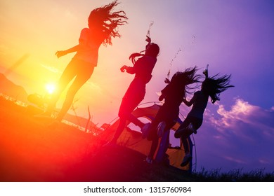 Silhouette Group of women camping,party with drink bottles and jumping enjoy travel trekking in vacation time at sunset.
