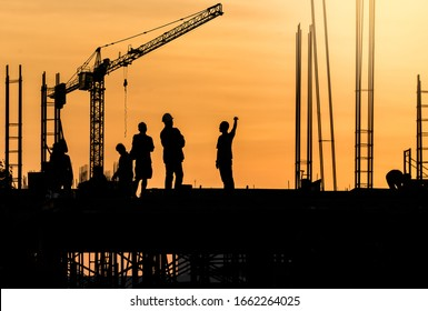 Silhouette group workers team on construction site and crane in the evening background.