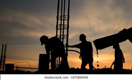 silhouette the group of workers working at a construction site.Construction workers work in preparation for binding rebar and concrete work