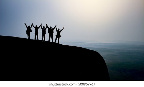 silhouette group of young people on top of the mountain