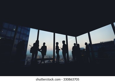 Silhouette of group of young skilled business people talking among themselves while standing in modern office interior near window, mans and women's purposeful bookkeepers discuss ideas after meeting