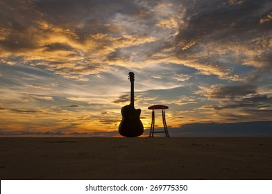 Silhouette Guitar with Chair at The Beach During Sunset Moment Image has grain or blurry or noise and soft focus when view at full resolution.  (Shallow DOF, slight motion blur)
