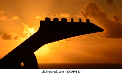Silhouette of guitar on sunset background