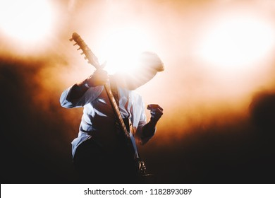 Silhouette of guitar player / guitarist perform on concert stage. Dark background, smoke, concert  spotlights