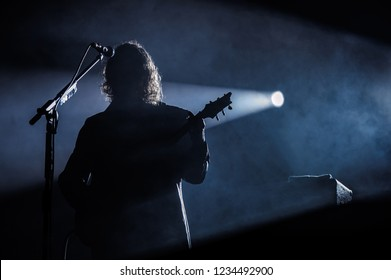 Silhouette of a guitar player on stage with microphone stand
