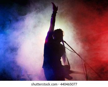 Silhouette of guitar player on stage. Dark background, smoke, spotlights