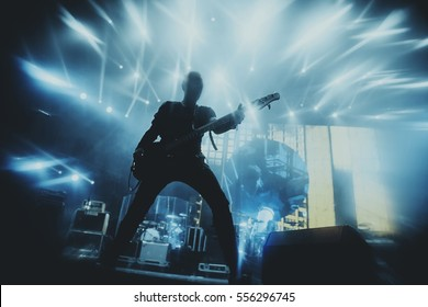 Silhouette of guitar player on stage. Dark background, smoke, concert  spotlights