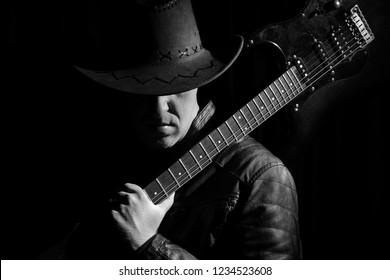 Silhouette of guitar player. Portrait of guitarist . Music concept, guitarist in dark. Black and white photo.