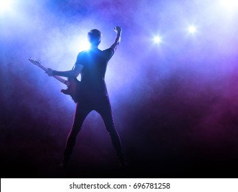 Silhouette of guitar player in stage lights