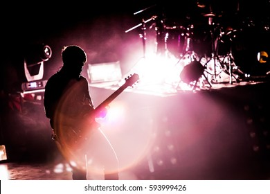 Silhouette of guitarist musician on stage at a concert.
