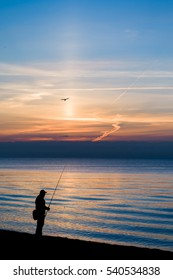 The silhouette of the guy with a fishing tackle, man standing at beautiful sunset beach view.